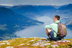 Freedom traveler man sitting upper the fjord and enjoying a beautiful nature Royalty Free Stock Photography