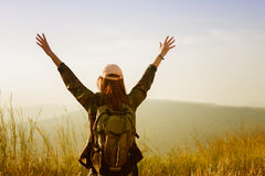 Freedom traveler woman standing with raised arms and enjoying a. Beautiful nature and cheering young woman backpacker at sunrise seaside mountain peak Royalty Free Stock Photography