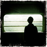 Freedom of traveling. A man watches the landscape from a window on a ferryboat Stock Image