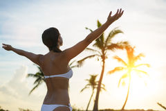 Freedom and tropical vacation. Blissful woman enjoying freedom and happiness on caribbean tropical vacation. Caucasian brunette raising arms towards the sunset Royalty Free Stock Images
