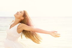 Freedom woman in free happiness bliss on beach. Smiling happy multicultural female model in white summer dress enjoying serene ocean nature during travel Royalty Free Stock Photos