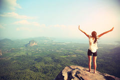 Freedom woman open arms on mountain peak Stock Photos