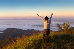 Freedom woman on top of mountain with flowing mist and beautiful. Sunset Royalty Free Stock Image