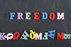FREEDOM word on black board background composed from colorful abc alphabet block wooden letters, copy space for ad text Stock Photography