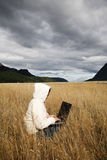 Freedom of Working Anywhere. Woman working with laptop in the middle of nowhere Royalty Free Stock Photography