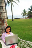 Freedom of Working Anywhere. Asian woman working on her vacation at the beach Royalty Free Stock Image