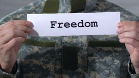 Freedom written on paper in hands of male soldier, release of war prisoners. Stock footage stock video