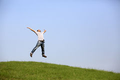 Freedom : Young man jumping over the field with outstretched hands. Royalty Free Stock Image