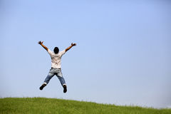 Freedom : Young man jumping over the field with outstretched hands. Royalty Free Stock Images