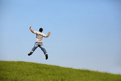 Freedom : Young man jumping over the field with outstretched hands. Royalty Free Stock Photos