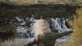 Freedom: young traveling woman looking on waterfalls in Iceland and raising hands up, feeling happy. Tourist female enjoying the beautiful landscape. Hair stock video