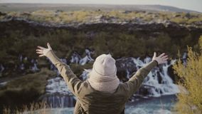 Freedom: young woman standing near waterfalls in Iceland and raising hands up, takes off hat and feeling happy. Traveling female enjoying the beautiful stock footage