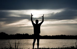 Freedome. Silhouette of man on the river, holding his hands up, hugging the sun Royalty Free Stock Image
