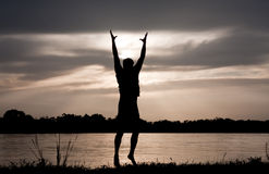 Freedome. Silhouette of man on the river, holding his hands up, hugging the sun Stock Photo