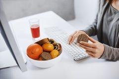 Freelance работая дома и имея закуску Подрезанный портрет женщины перед компьютером, держа печенье и печатать Стоковое фото RF