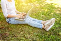 Woman legs on green grass lawn in city park, hands working on laptop pc computer. Freelance business concept stock images