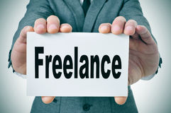 Freelance. Businessman showing a signboard with the word freelance written in it stock photo