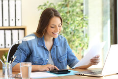 Freelance calculating a budget. Freelance woman calculating a budget in a desktop at office Stock Photos