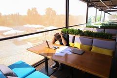 Freelance copywriter przepisać tekst na laptopie przy kawiarnia stołem zdjęcia stock