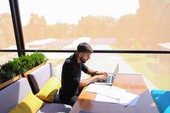 Freelance copywriter przepisać tekst na laptopie przy kawiarnia stołem obrazy stock