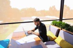 Freelance copywriter przepisać tekst na laptopie przy kawiarnia stołem fotografia stock