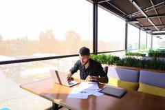 Freelance copywriter przepisać tekst na laptopie przy kawiarnia stołem obraz stock