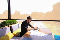 Freelance copywriter rewrite text on laptop at cafe table. Freelance copywriter typing text fast on laptop keyboard at cafe table and looking tired. Handsome Royalty Free Stock Photo