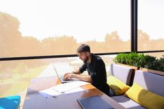Freelance copywriter rewrite text on laptop at cafe table. Freelance copywriter typing text fast on laptop keyboard at cafe table and looking tired. Handsome Stock Photo