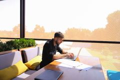 Freelance copywriter rewrite text on laptop at cafe table. Freelance copywriter typing text fast on laptop keyboard at cafe table and looking tired. Handsome Royalty Free Stock Image