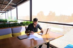 Freelance copywriter rewrite text on laptop at cafe table. Freelance copywriter typing text fast on laptop keyboard at cafe table and looking tired. Handsome Stock Images