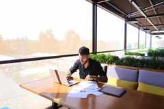 Freelance copywriter rewrite text on laptop at cafe table. Freelance copywriter typing text fast on laptop keyboard at cafe table and looking tired. Handsome Stock Image