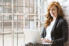 Freelance copywriter sitting on windowsill. Happy young freelance copywriter women using laptop sitting on windowsill Stock Image