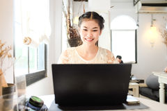 Freelance e business asian women using laptop computer in coffee Royalty Free Stock Images