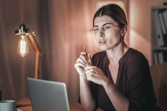 Musing female freelancer editing article. Freelance experience. Reflective female freelancer using laptop and wearing glasses royalty free stock photo