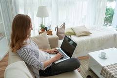 Copywriter. Freelance female copywriter typing on laptop when sitting on sofa Stock Image