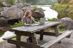 Freelance girl working on laptop in nature. And beautiful landscapes Royalty Free Stock Image