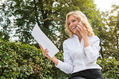 Freelance lady speaking over mobile phone oudoors Royalty Free Stock Photo