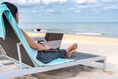 Freelance lady using laptop on the beach royalty free stock photos