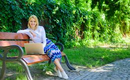 Freelance lifestyle advantages. Working outdoors. Casual and part time outdoor jobs. Girl sit bench with notebook. Woman. With laptop works in park enjoy green royalty free stock images