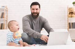 Businessman working from home and watching child stock photo