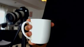 Freelance photographer holding cup of coffee with dslr camera in background stock video footage