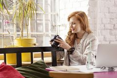 Freelance photographer in industrial interior. Redhead female freelance photographer drinking water in industrial interior Royalty Free Stock Images