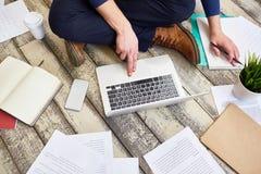 Freelance Translator Working on Floor. Top view of unrecognizable freelancer working sitting cross legged on wooden floor, using laptop computer Stock Photos