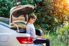Freelance use notebook for send jobs to customers. Young asian woman sitting on hatchback car with notebook, Freelance use notebook for send jobs to customers Royalty Free Stock Images