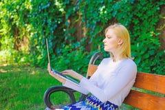 Freelance voordelen De vrouw met laptop werkt openlucht, groene aardachtergrond Dame die freelancer in park werken royalty-vrije stock afbeelding