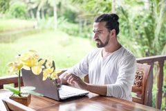 Freelance work on laptop. Man sitting at wooden desk inside garden working on computer. Freelance work on laptop. Casual dressed man sitting at wooden desk Royalty Free Stock Photos