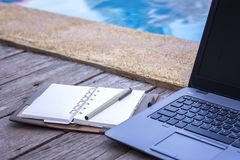 Freelance working everywhere every time. Working everywhere every time, Laptop beside a pool with empty notebook and pen royalty free stock photo