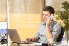 Freelance working on line and talking on phone. While is searching information in a laptop sitting in a desk at office Royalty Free Stock Image