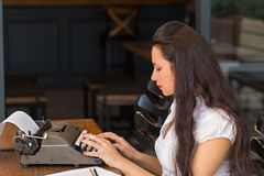 Freelance and writing concept. Female writer typing on a retro t. Freelance and writing concept. eview potrait of a female writer working in dark interior using royalty free stock image