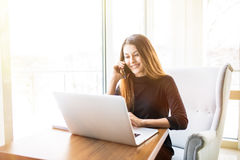 Freelance young smile woman sitting in the cafeteria with laptop and using mobile phone Royalty Free Stock Photography